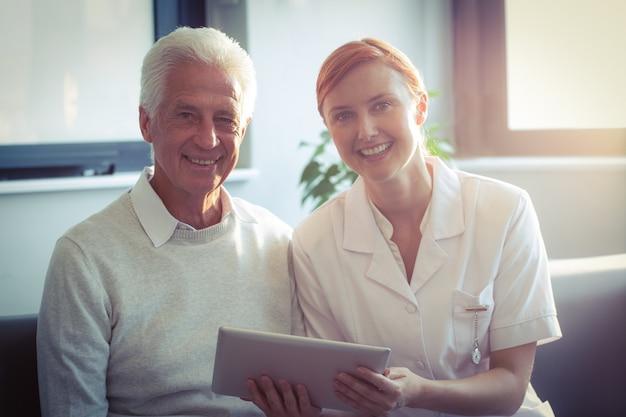 Enfermera mostrando informe médico al hombre mayor en tableta digital Foto Premium