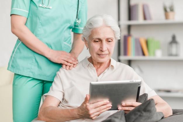 Enfermera de pie cerca de mujer senior con tableta digital Foto gratis