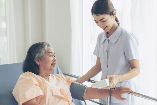 Enfermera que mide la presión arterial de una anciana mayor en pacientes en cama de hospital - concepto senior médico y sanitario Foto gratis