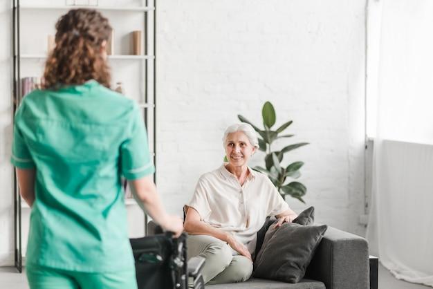 Enfermera con silla de ruedas frente de ion frente de paciente femenino feliz Foto gratis