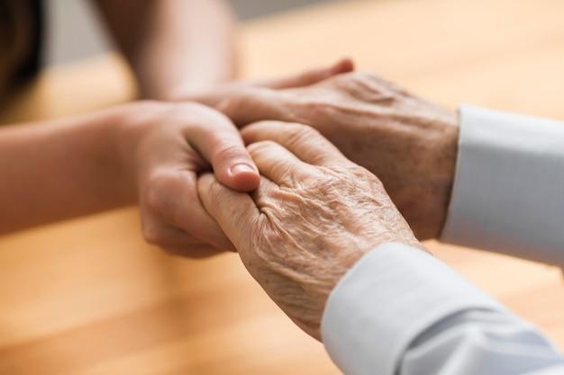 Enfermera sosteniendo las manos del hombre mayor de empatía Foto gratis