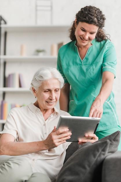Enfermera con su paciente viendo video en tableta digital Foto Premium