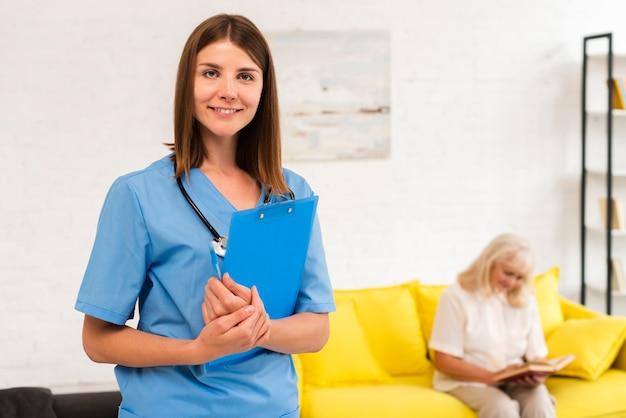 Enfermera de tiro medio con portapapeles azul mirando a la cámara Foto gratis