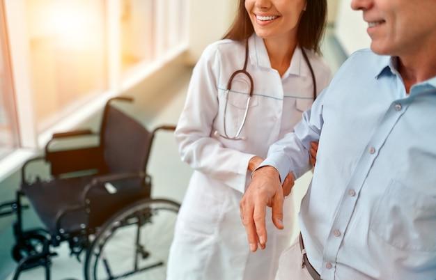 Una enfermera con uniforme médico ayuda a un paciente discapacitado maduro en silla de ruedas a aprender a caminar de nuevo. rehabilitación de una persona discapacitada en la clínica. Foto Premium