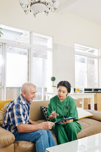 Enfermera visitando paciente anciano en casa Foto Premium