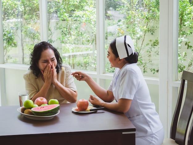 Las enfermeras están alimentando manzanas a los ancianos, las mujeres mayores no quieren comer fruta Foto Premium