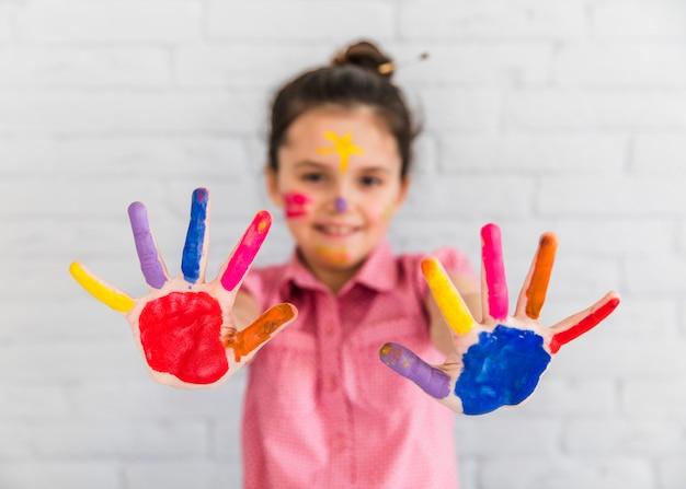 Enfoque selectivo de una niña mostrando manos pintadas de colores. Foto gratis