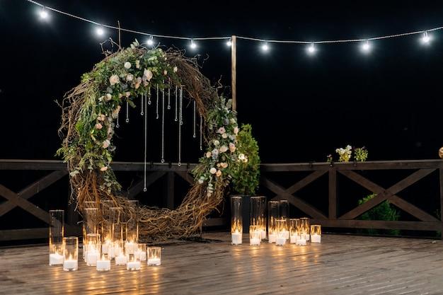 Enorme círculo decorativo hecho de sauce, vegetación y rosas de color naranja pálido con velas encendidas Foto gratis