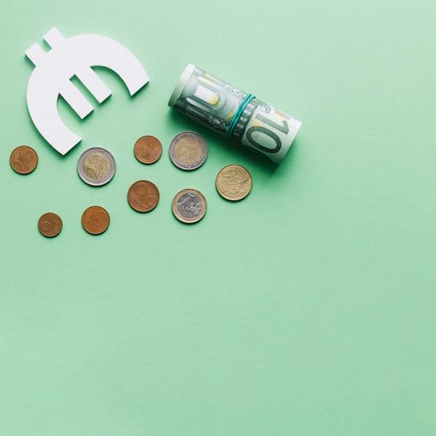 Enrollado billete de cien euros con símbolo y monedas sobre fondo verde Foto gratis