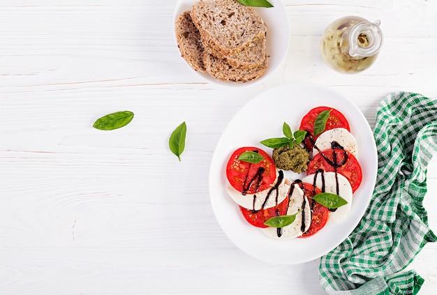Ensalada caprese italiana tradicional con mozzarella, tomate, albahaca y vinagre balsámico. vista superior, arriba Foto Premium