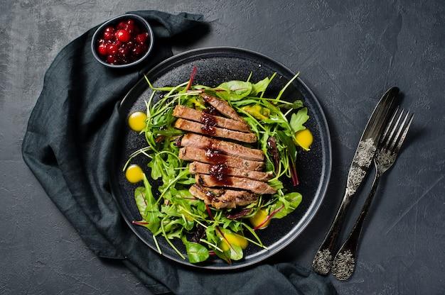 Ensalada con filete de ternera, rúcula y acelgas en un plato negro. Foto Premium