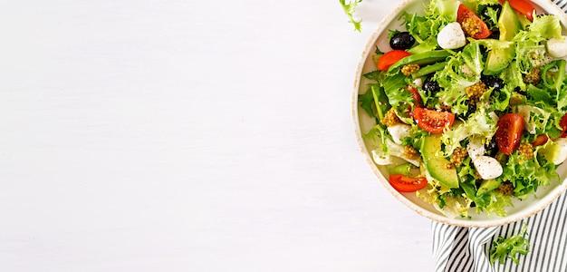Ensalada fresca con aguacate, tomate, aceitunas y mozzarella en un tazón. Foto Premium