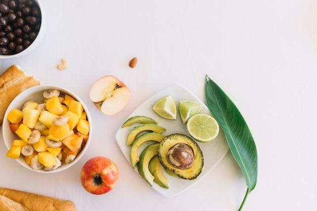 Ensalada de frutas y pan sobre fondo blanco Foto gratis