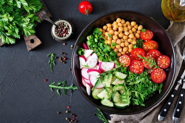 Ensalada de garbanzos, tomates, pepinos, rábanos y verduras. comida dietética ensalada vegana vista superior. endecha plana. tazón de buda Foto Premium