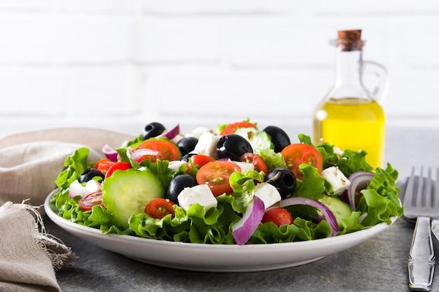 Ensalada griega fresca en un tazón con aceituna negra, tomate, queso feta, pepino y cebolla Foto Premium