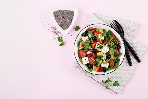 Ensalada griega con pepino, tomate, pimiento dulce, lechuga, cebolla verde, queso feta y aceitunas con aceite de oliva. comida sana. vista superior Foto gratis