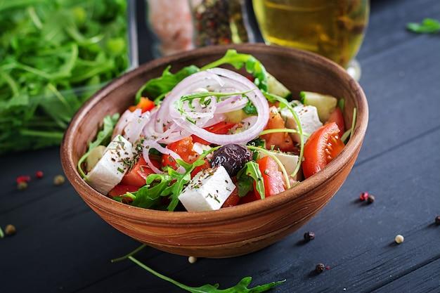 Ensalada griega con tomate fresco, pepino, cebolla roja, albahaca, queso feta, aceitunas negras y hierbas italianas Foto gratis