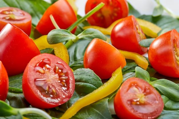 Ensalada con hojas de albahaca, tomates cherry y pimiento en un plato blanco. primer plano, enfoque selectivo Foto Premium
