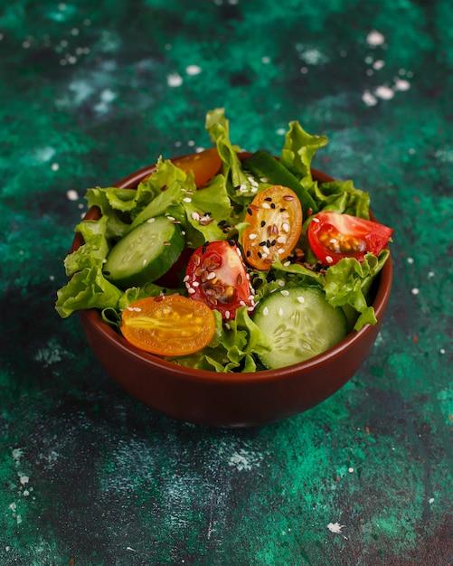 Ensalada de lechuga fresca con tomates amarillos, rodajas, tomates cherry, tazón de semillas en la oscuridad, Foto gratis
