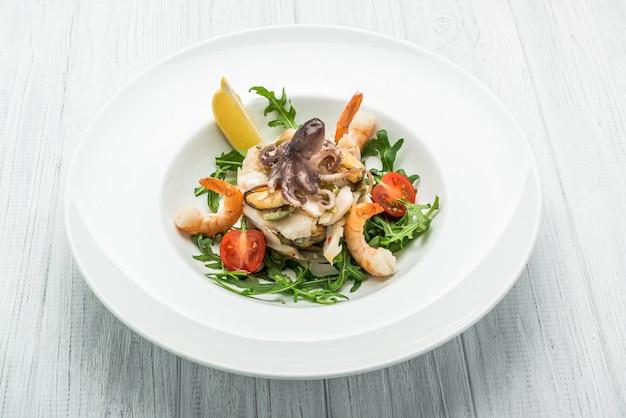 Ensalada de mariscos y vegetales con rúcula y tomates. Foto Premium