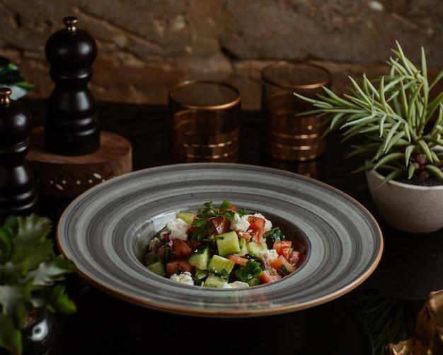 Ensalada mixta de verduras cortada en formas cuadradas dentro de un plato gris Foto gratis