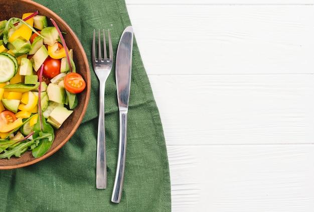 Ensalada mixta de verduras con un tenedor y un cuchillo en un mantel verde sobre un escritorio blanco Foto gratis