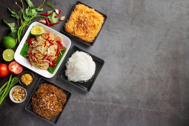 Ensalada de papaya servida con fideos de arroz y ensalada de verduras decorada con ingredientes de la comida tailandesa. Foto gratis