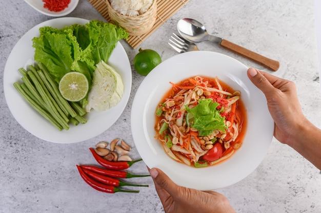 Ensalada de papaya tailandesa en un plato blanco con arroz y camarones secos Foto gratis