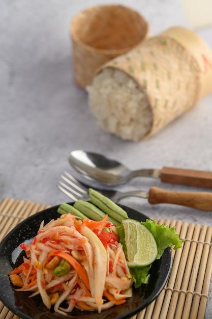 Ensalada de papaya tailandesa en un plato negro con arroz pegajoso Foto gratis