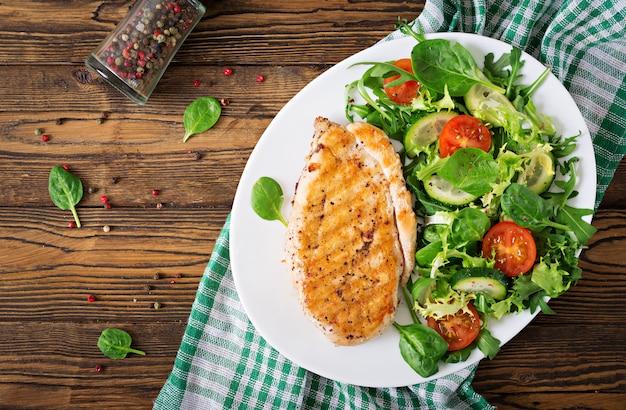 Ensalada de pechuga de pollo a la parrilla y vegetales frescos: tomates, pepinos y hojas de lechuga. ensalada de pollo. comida sana. endecha plana. vista superior Foto gratis
