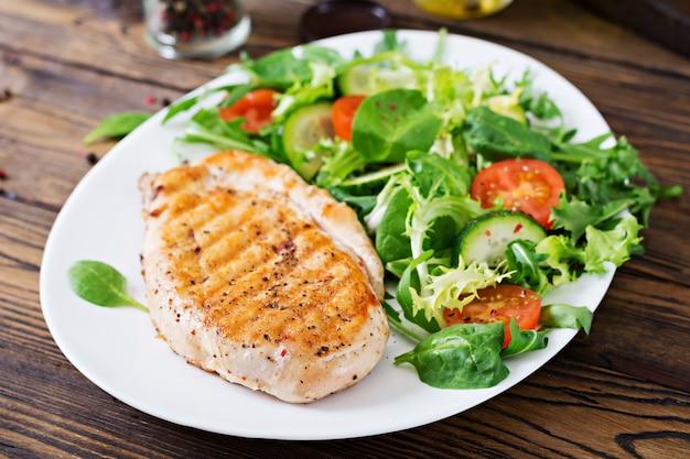 Ensalada de pechuga de pollo a la parrilla y vegetales frescos: tomates, pepinos y hojas de lechuga. ensalada de pollo. comida sana. Foto gratis