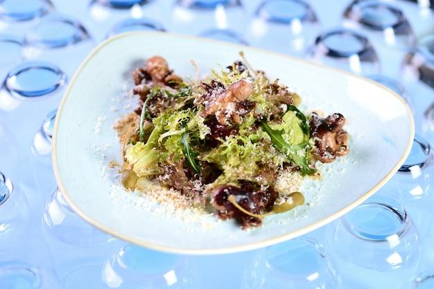 Ensalada de pulpo, rúcula, alcaparras y queso rallado. Foto Premium