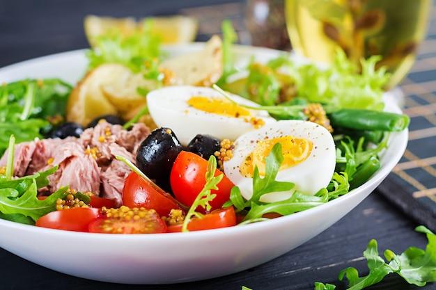 Ensalada saludable de atún, judías verdes, tomates, huevos, papas, aceitunas negras de cerca en un recipiente sobre la mesa Foto gratis
