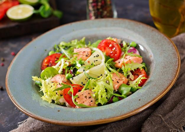 Ensalada saludable con pescado. salmón al horno, tomate, lima y lechuga. cena saludable. Foto gratis