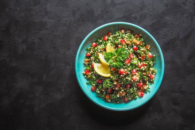 Ensalada tabulé con cuscús en un recipiente sobre la mesa negra. ensalada vegetariana levantina con perejil, menta, bulgur, tomate. Foto Premium