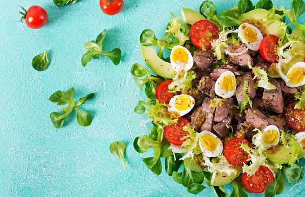 Ensalada tibia de hígado de pollo, aguacate, tomate y huevos de codorniz. cena saludable. menú dietético endecha plana. vista superior Foto gratis