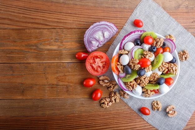 Ensalada con tomates cherry, queso mozzarella, aceitunas, kiwi y nueces sobre fondo de madera marrón. Foto Premium
