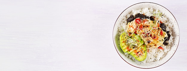 Ensalada vegana con arroz, col de kimchi en escabeche, aguacate, nori y sésamo en un tazón. Foto gratis
