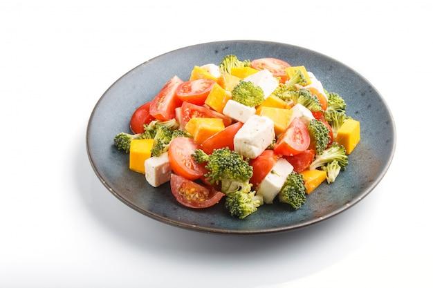 Ensalada vegetariana con brócoli tomates queso feta y calabaza en un plato de cerámica azul aislado sobre fondo blanco. Foto Premium