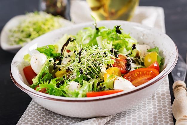 Ensalada vegetariana con tomate cherry, mozzarella y lechuga. Foto gratis