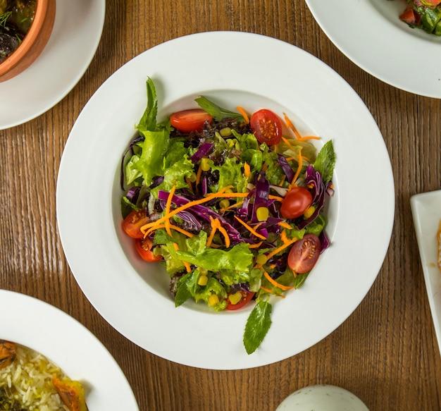 Ensalada verde de verano fresco con hierbas y tomates. Foto gratis