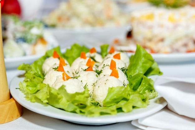 Ensaladas en una mesa de banquete blanco Foto Premium
