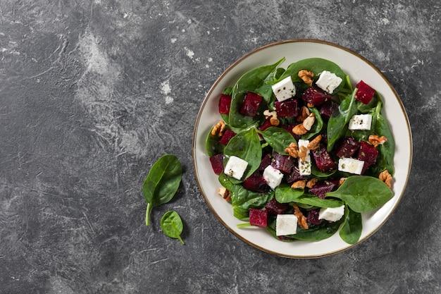 Ensaladas vegetarianas de carpaccio de remolacha con espinacas, albahaca, aceite de oliva, queso de cabra, nueces. vista superior, espacio. alimentación saludable. Foto Premium