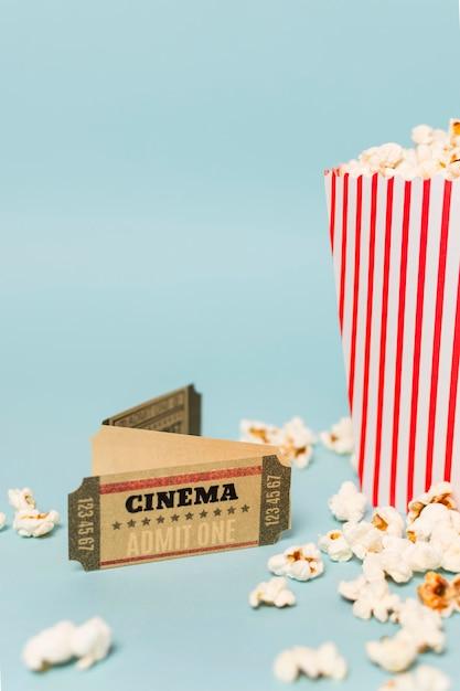Entradas de cine con palomitas de maíz sobre fondo azul. Foto gratis