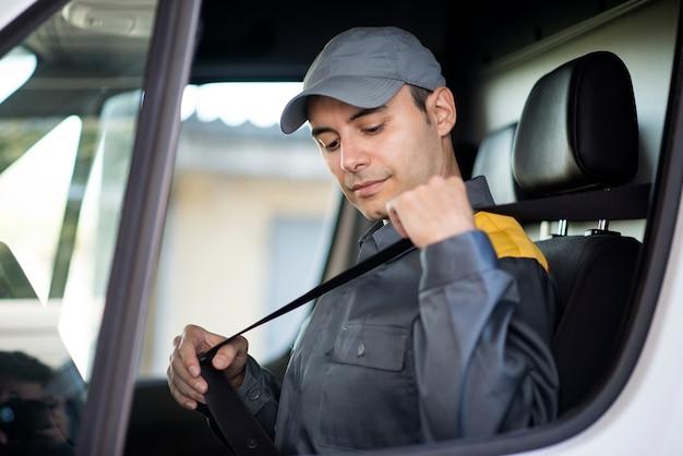Entregador poniéndose el cinturón de seguridad en su camioneta. Foto Premium