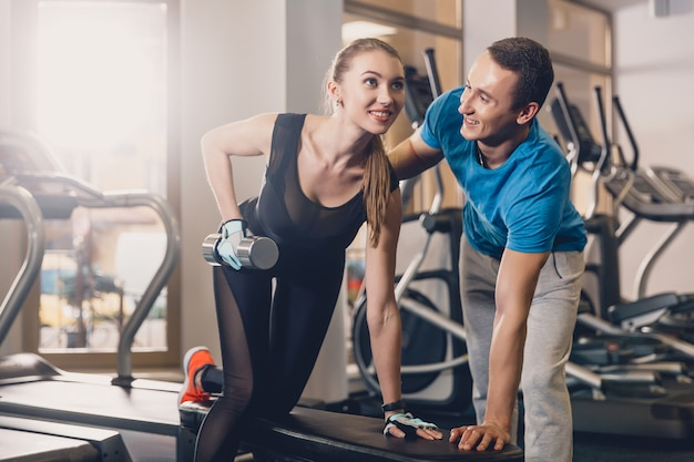 El entrenador ayuda a la niña a hacer el ejercicio. Foto Premium