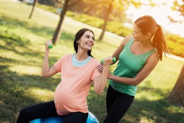Un entrenador en una camiseta verde ayuda a una mujer embarazada en una rosa Foto Premium