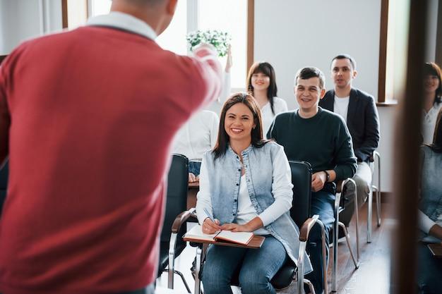 Entrenador divertido. grupo de personas en conferencia de negocios en el aula moderna durante el día Foto gratis