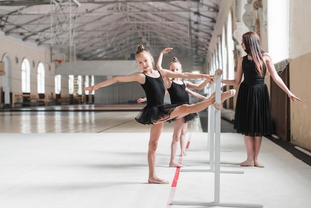 Entrenador femenino que mira a las muchachas de la bailarina que estiran su pierna en la barra Foto gratis