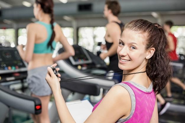 Entrenador femenino sonriendo a la cámara en el gimnasio Foto Premium